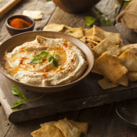 Creamy Hummus drizzle with olive oil and sprinkled with paprika on a wooden board with pita chips
