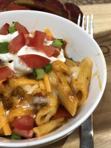 Cooked Penne Pasta, Ground Beef with Salsa Tomato Sauce topped with sour cream, green onions diced tomatoes and cheese