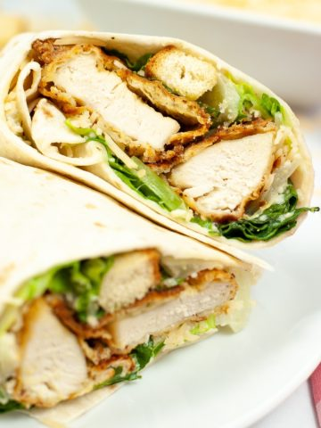 Golden friend chicken tenders with caesar dressing, croutons, romaine lettuce, wrapped in a flour tortilla