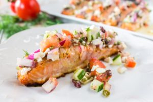 Baked Salmon with Greek Salsa on a white plate. Platter of salmon in the background