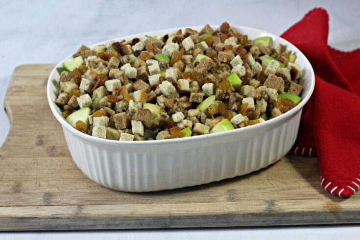 Sausage Apple Stuffing in a white ceramic oval baking dish ready to be baked