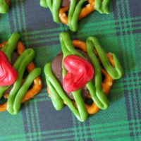 Square pretzels with a chocolate kiss melted on top and topped with green candy melt in a zig zag pattern and a red candy heart
