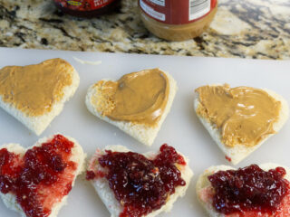 White bread slices cut into heart shapes with peanut butter and jelly on them.