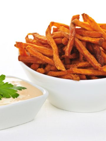 A bowl of crisp sweet potato fries and a small white bowl of fry sauce with parley on top